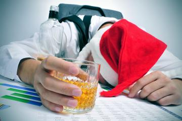 a man with a santa hat sleeping in his desk after an office christmas party