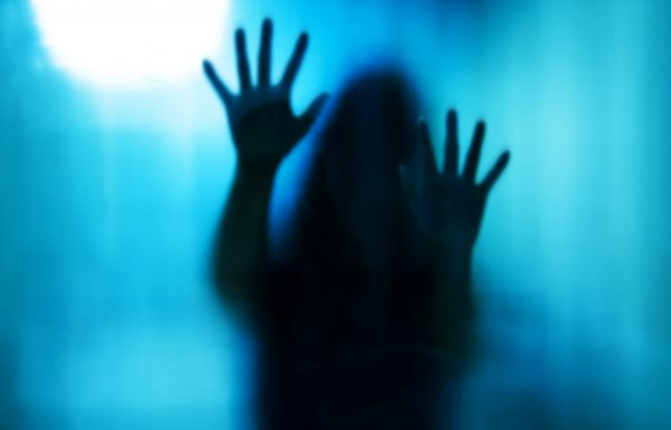 Abstract woman behind the matte glass. Blurry hand and body figure