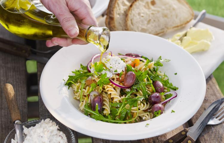 Pouring olive over pasta meal