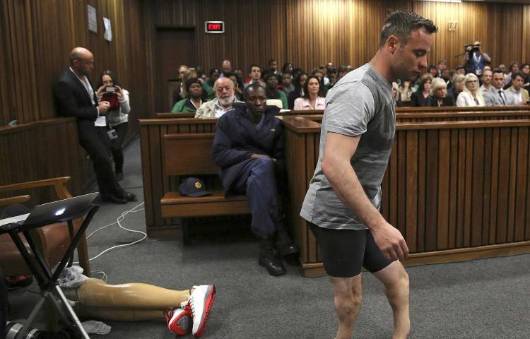 FILE - Oscar Pistorius' prosthetics lie on the floor as he walks on his amputated legs during argument in mitigation of sentence by his defense attorney Barry Roux in the High Court in Pretoria, South Africa, on June 15, 2016. An appeals court found Pistorius guilty of murder and not a lesser charge of culpable homicide for the shooting death of his girlfriend Reeva Steenkamp. (Siphiwe Sibeko via AP, Pool, File)
