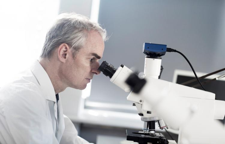 Male meteorologist looking through microscope in weather station laboratory