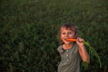 Portrait of young girl, eating freshly picked carrot