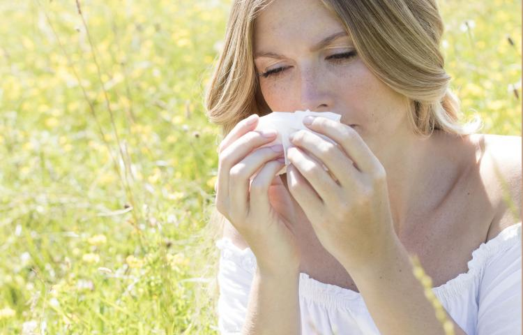 MODEL RELEASED. Young woman blowing nose on tissue.