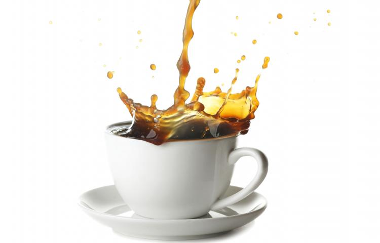 Pouring coffee with splash in cup isolated on white background