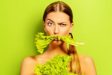 Pretty cheerful young woman posing with fresh green lettuce leaves. Healthy eating concept. Dieting.