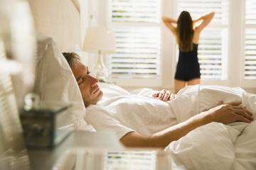 Wife stretching at morning window behind husband sleeping in bed