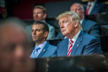 """7/20/2016, Cleveland---Day 3 of the RNC, Republican National Convention. Donald Trump listens to the speeches, next to him his son Donald John """"Don"""" Trump Jr.  Photo Rene Clement"""