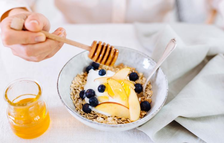 Woman drizzling honey onto bowl of breakfast cereal topped with fruit