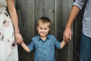 Cropped view of boy holding parents hands