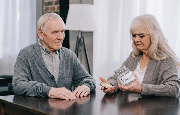 upset senior couple sitting at table and holding empty glass jar with 'pension' lettering