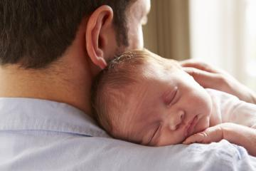 Father At Home With Sleeping Newborn Baby Daughter
