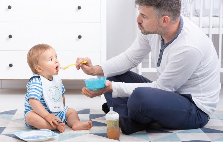 Shot of a dad sitting on a floor and feeding his little baby