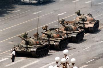 """FILE - In this June 5, 1989 file photo, a Chinese man stands alone to block a line of tanks heading east on Beijing's Cangan Blvd. in Tiananmen Square.  The man, calling for an end to the recent violence and bloodshed against pro-democracy demonstrators, was pulled away by bystanders, and the tanks continued on their way.  The Chinese government crushed a student-led demonstration for democratic reform and against government corruption, killing hundreds, or perhaps thousands of demonstrators in the strongest anti-government protest since the 1949 revolution. Ironically, the name Tiananmen means """"Gate of Heavenly Peace"""". (AP Photo/Jeff Widener, File)"""