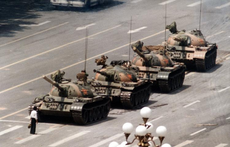 "FILE - In this June 5, 1989 file photo, a Chinese man stands alone to block a line of tanks heading east on Beijing's Cangan Blvd. in Tiananmen Square.  The man, calling for an end to the recent violence and bloodshed against pro-democracy demonstrators, was pulled away by bystanders, and the tanks continued on their way.  The Chinese government crushed a student-led demonstration for democratic reform and against government corruption, killing hundreds, or perhaps thousands of demonstrators in the strongest anti-government protest since the 1949 revolution. Ironically, the name Tiananmen means ""Gate of Heavenly Peace"". (AP Photo/Jeff Widener, File)"