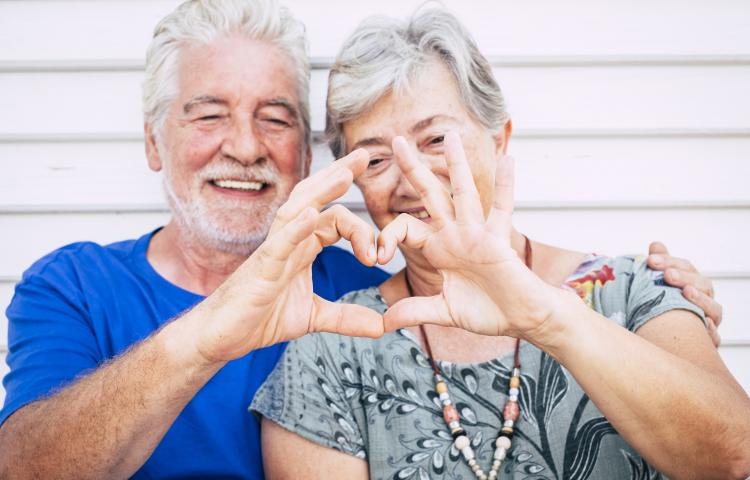 playful beautiful cheerful caucasian adult senior couple enjoying lifestyle toghetner with smile and laugh doing heart with hands. love and partnership forever concept for happy man and woman people