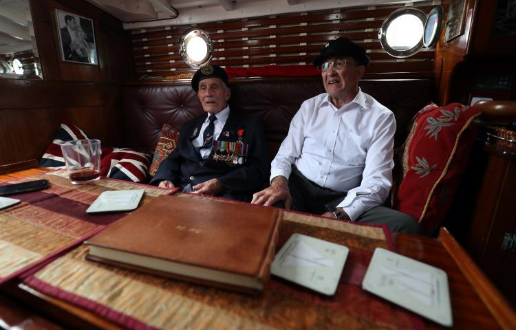 D-Day veteran John Dennett, 94, (left) sits with skiipper Ian Gilbert as he looks around the boat Lady Lou which was used in the Dunkirk evacuation, during a D-Day event at Portsmouth Historical Dockyard.