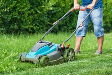 Man mowing the lawn with blue lawnmower in summertime - closeup