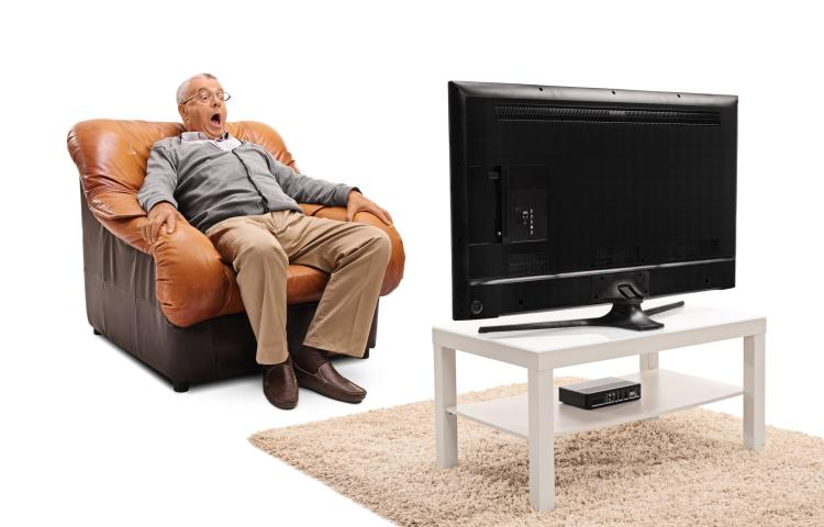 Terrified senior watching a scary movie on TV seated on an armchair isolated on white background
