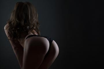 Young woman in lingerie posing back studio shot on dark bg