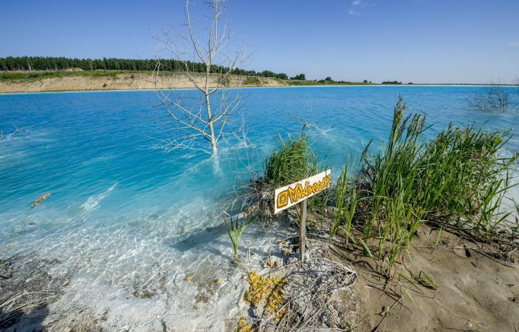 """In this Friday, July 12, 2019 photo, a sign board reading """"Maldives"""" is displayed by a lake in the Siberian city of Novosibirsk, about 2,800 kilometers (1,750 miles) east of Moscow, Russia.  Thousands of Novosibirsk residents, from scantily clad women to newlyweds have been instagramming selfies near the lake nicknamed the """"Siberian Malvides"""" after the far-flung tropical islands in the Indian Ocean. This is in fact is a man-made dumb of coal from a nearby power station that provides for most of Novosibirsk's energy needs. (AP Photo/Ilnar Salakhiev)"""