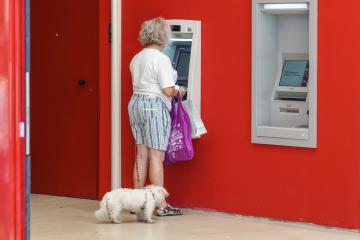 NICE , FRANCE - 15 August 2017 : an unidentified elderly lady makes a withdrawal at the cash desk in a bank near the mall .