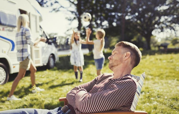 Serene father resting in lounge chair with family playing in background outside sunny motor home