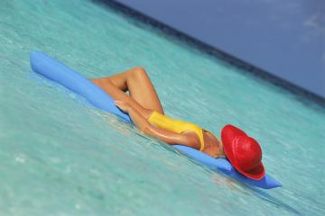Woman with red hat lying on blue air mattress in aqua lagoon