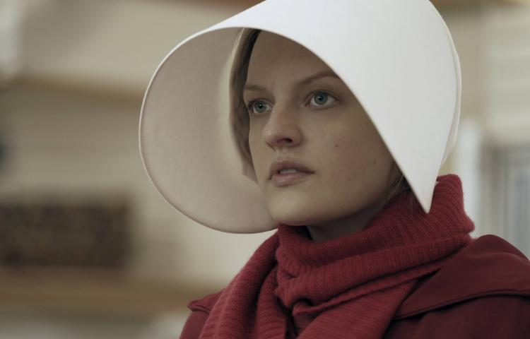 "This image released by Hulu shows Elisabeth Moss as Offred in a scene from the critically acclaimed, ""The Handmaid's Tale."" Nominations for the 75th annual Golden Globes will be announced on Monday, Dec. 11, 2017. (George Kraychyk/Hulu via AP)"