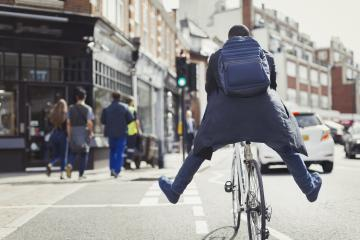 Playful young businessman commuting, riding bicycle on sunny urban street