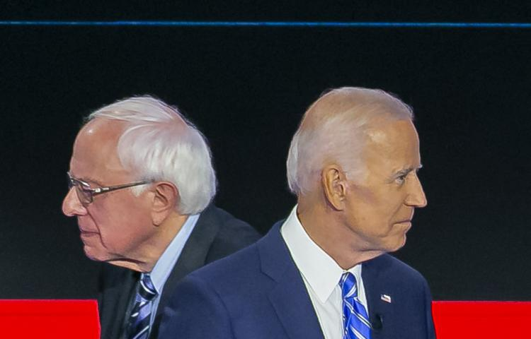 Democratic presidential candidate Sen. Bernie Sanders (I-Vt.), left, walks past former Vice President Joe Biden during a commercial break during the second night of the first Democratic presidential debate on Thursday, June 27, 2019, at the Arsht Center for the Performing Arts in Miami. (Al Diaz/Miami Herald/TNS/ABACAPRESS.COM)